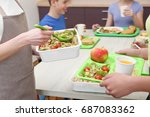 Stock photo young woman serving lunch to children at school canteen 687083362
