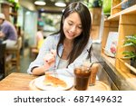 young woman enjoy her food in... | Shutterstock . vector #687149632