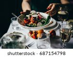 hands passing over a bowl of... | Shutterstock . vector #687154798