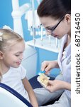 A young dentist shows a child how to brush their teeth - stock photo