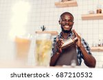 Stock photo smiling handsome african american bartender making cocktail in shaker on bar counter 687210532