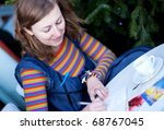 Beautiful girl in bright clothes writing postcards in cafe - stock photo