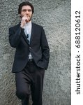 Small photo of White caucasian handsome bearded man in the suit and white shirt smoking cigarette. Clothes advertising campaign concept.