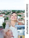 Small photo of closeup portrait of young woman looking sky above the city and feeling free, man holding wife and playing to feel adrenaline, relaxation on the big height or altitude
