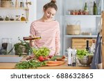 woman adding olive oil to her... | Shutterstock . vector #688632865