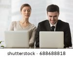 Small photo of Interested curious corporate spy looking at colleagues laptop, spying on rival, cheating on examination, stealing idea, sneaking peek, taking inquisitive glance at computer screen of unaware coworker