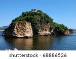 Rocky islet with tropical vegetation against blue sky - stock photo