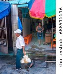 Small photo of Belen, Peru - May 17, 2016: Peruvian man carrying the alive hen on the street of Iquitos, Belen