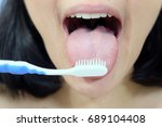 woman cleaning tongue using... | Shutterstock . vector #689104408