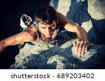 men climbs a rock on the sunset ... | Shutterstock . vector #689203402