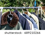 Small photo of women and men coats and jackets on rack display at garage sale or thrift store to resale, reuse, recycle or exchange outdoor