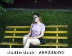 Small photo of A young fashionable girl with glasses, a student, bob haircut, in short shorts, a pink T-shirt, sits on a yellow bench, in the street in the summer, in the park.
