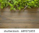 fresh mint leaves on wood... | Shutterstock . vector #689371855