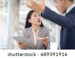 Small photo of Young businesswoman holding papers talking with a businessman with anger, Boss found a mistake in documentation. Work failure concept.