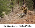 Small photo of female hunter with binoculars ready to hunt, holding gun and walking in forest.