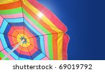Beach umbrella against sunny blue sky on a summer day. Copy space. - stock photo