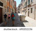 family walks through the narrow ...   Shutterstock . vector #690352156