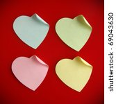 Background of four heart-shaped colorful post its over red - stock photo