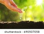 male hand giving water to young ... | Shutterstock . vector #690507058