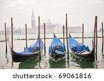 Three gondolas in Venice at the pier - stock photo