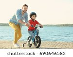 young man teaching his son to... | Shutterstock . vector #690646582