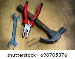 pliers on a hammer with nails... | Shutterstock . vector #690705376