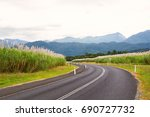 Small photo of A tall crop of Sugar Cane growing on both sides of a road in tropical Far North Queensland, Australia. Forest and mountains beyond.