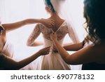 bridesmaids buttoning dress at... | Shutterstock . vector #690778132