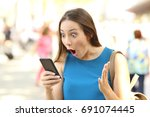 amazed woman receiving shocking ... | Shutterstock . vector #691074445