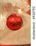 beautiful red ornament hanging from white christmas tree - stock photo