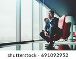 Small photo of Adult pensive and anxious businessman in blue formal suit is sitting on red armchair in luxury office interior near window and recapitulating recent work meeting with copy space zone for advertising