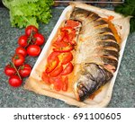 baked silver carp with tomatoes. | Shutterstock . vector #691100605