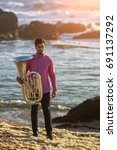 Small photo of Musician with trumpet on the sea coast during surf. Tuba instrument.