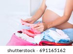 pregnant woman packing suitcase ... | Shutterstock . vector #691165162