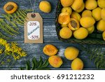 """Small photo of Delicious ripe apricots in a wicker basket green, Wild flowers, fern leaves And the price tag with the message """"discounts"""" and interest. Top view. On a wooden table background. Summer sales concept."""