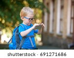 Small photo of Cute clever boy in glasses with school bag and smartphone in hands outdoors. Education in elementary school with cell phone. New technology. Excessive use of cell phone. Back to school.