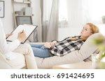 depressed woman lying on sofa... | Shutterstock . vector #691424695