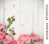 Small photo of vintage styled image of pink roses lying on white wooden background, with copy space, inspired by flat lay style