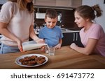 mom with son and daughter eat... | Shutterstock . vector #691473772