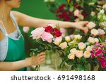female florist making beautiful ... | Shutterstock . vector #691498168