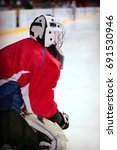 Small photo of Hockey goalie in generic red equipment protects gate
