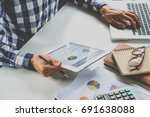 Small photo of Businessman working with digital tablet and book and document on wooden desk in modern office.Business analysis and strategy concept.