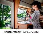 woman cooking in camper ... | Shutterstock . vector #691677382