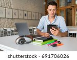 young handsome man sitting at... | Shutterstock . vector #691706026