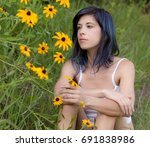 Pretty Woman Sitting in Grass Beside Flowers