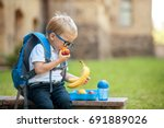 cute schoolboy eating outdoors... | Shutterstock . vector #691889026