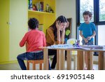 Small photo of teacher kindergarten hands closed both ears of her in an upset of failed to quell quited naughty, of the boys in class at preschool kids argument