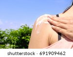 Small photo of Women apply sunscreen to the shoulder protect from UV rays.Very sun light city sky background.