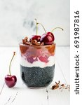 Small photo of Healthy Black Forest dessert. Black activated charcoal chia pudding with cherries, coconut cream and chocolate. Vegan creamy breakfast. Copy space background