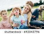 happy young family blowing soap ... | Shutterstock . vector #692043796